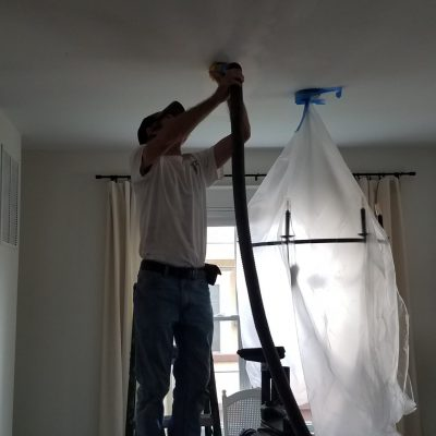 Interior painting in Frederick shows man sanding with vacuum attachment